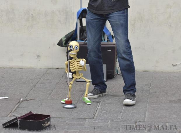 A skeleton performs for curious onlookers as they admire the artistry of a puppeteer busking in Valletta's busy streets on November 21. Photo: Mark Zammit Cordina