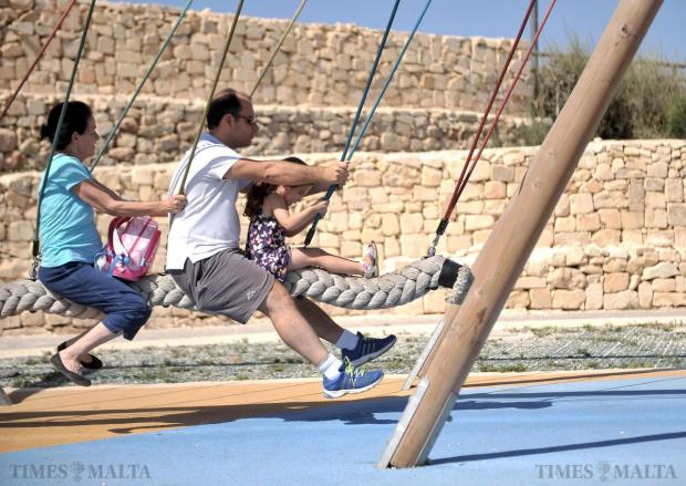 A family uses a swing at the Family Park in Marsascala on August 25. Photo: Chris Sant Fournier