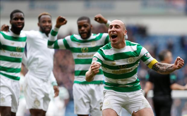 Celtic players celebrate their victory over Rangers at Ibrox Park.