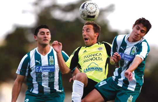 Marsaxlokk's Peter Pullicino (centre) gets first to the ball against Floriana.