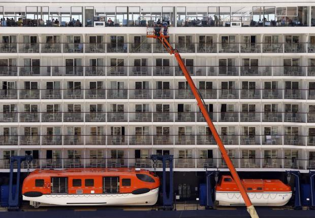Crew members use a crane while cleaning windows on the cruise liner Mein Schiff 3 in Valletta's Grand Harbour on June 28. Photo: Darrin Zammit Lupi