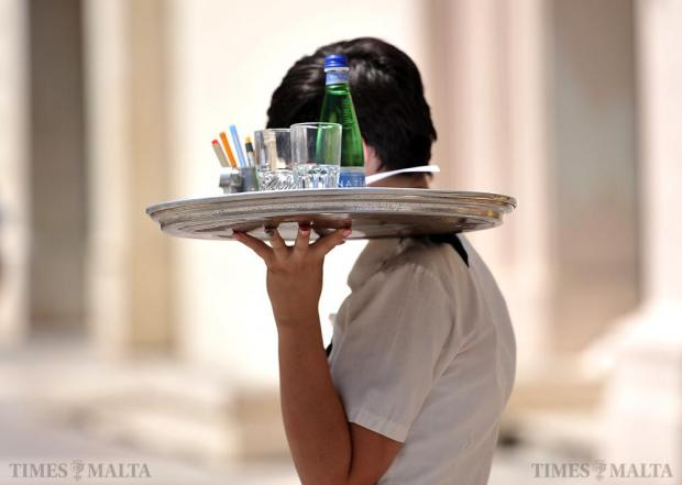 A waitress carries a tray across Republic Street in Valletta on August 17. Photo: Chris Sant Fournier