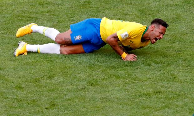 Brazil's Neymar lies on the pitch after sustaining an 'injury'.