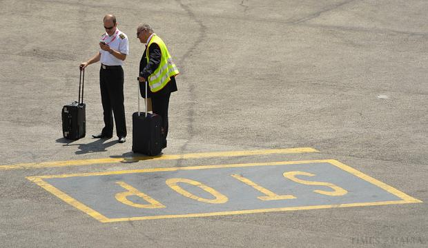 An Air Malta pilot waits for other crew members on arrival at Malta International Airport on August 26. The pilots are under a pilots' association directive to dress down for flights – not to wear the jacket, tie and hat. Photo: Matthew Mirabelli