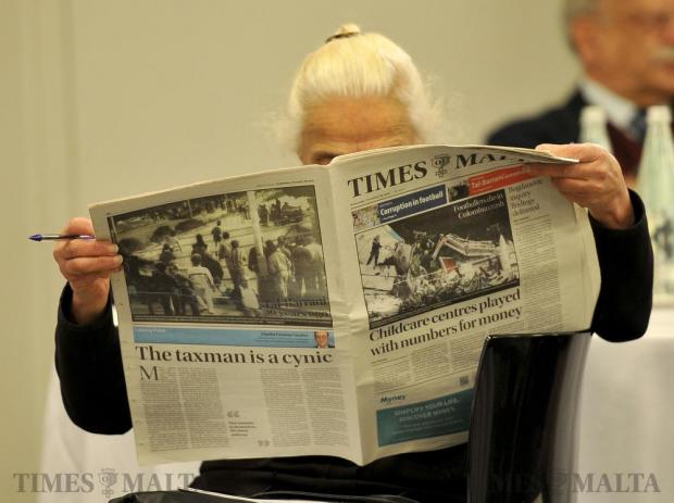A woman reads the Times of Malta newspaper at the debate organized by The Times of Malta on November 30. Photo: Chris Sant Fournier