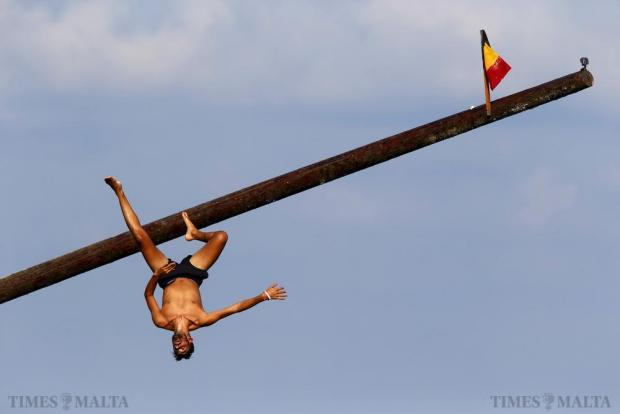 """A man falls acrobatically as he slips on the """"gostra"""", a pole covered in grease, during the celebrations for the religious feast of St Julian, patron of the town of St Julian's on August 30. In the traditional """"gostra"""", young men, women and children have to make their way to the top of a pole and try to uproot one of the flags to win prizes. Photo: Darrin Zammit Lupi"""