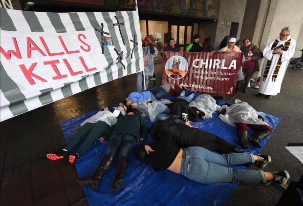 """mmigrant rights leaders and clergy hold a """"Walls Kill"""" die-in to protest against the building of the wall on the border with Mexico, outside City Hall in Los Angeles, California."""