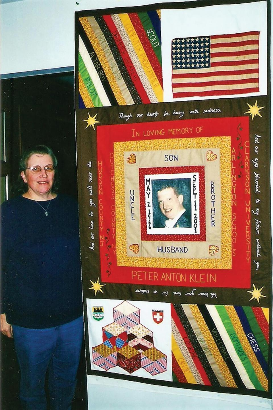 Ruth Klein posing beside the quilt she crafted in memory of her son Peter, who died during the September 11 attacks.
