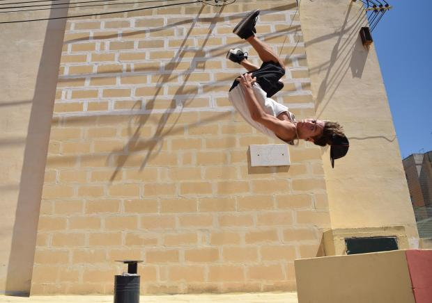 A teenager performs a summersault over a wall in Kalkara whilst practicing Parkour on July 10. Photo: Mark Zammit Cordina