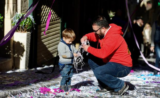 A child and his father play with paper cuttings before the band procession arrives in St Paul Street for the afternoon march in Valletta on February 10 Photo: Steve Zammit Lupi