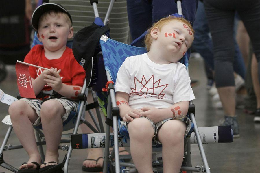A toddler takes a nap with patriotic stickers on his body during the Canada Day celebration at Canada Place in Vancouver, Canada, July 1, 2017. Photo: Xinhua