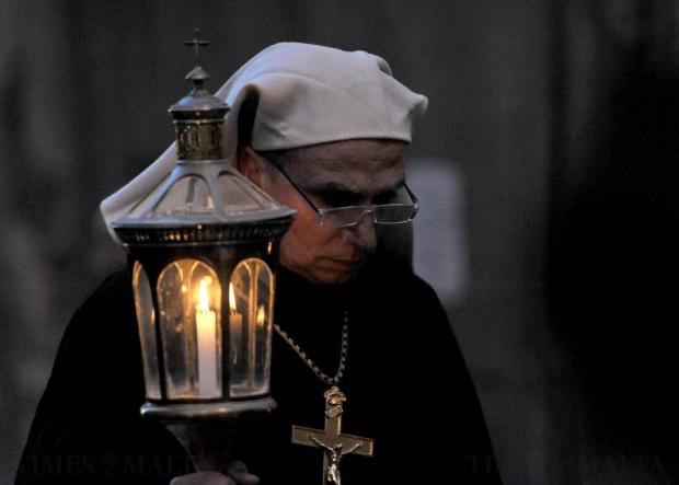 A participant carries a candle at the Our Lady of Sorrows procession in Valletta on March 18. Photo: Chris Sant Fournier
