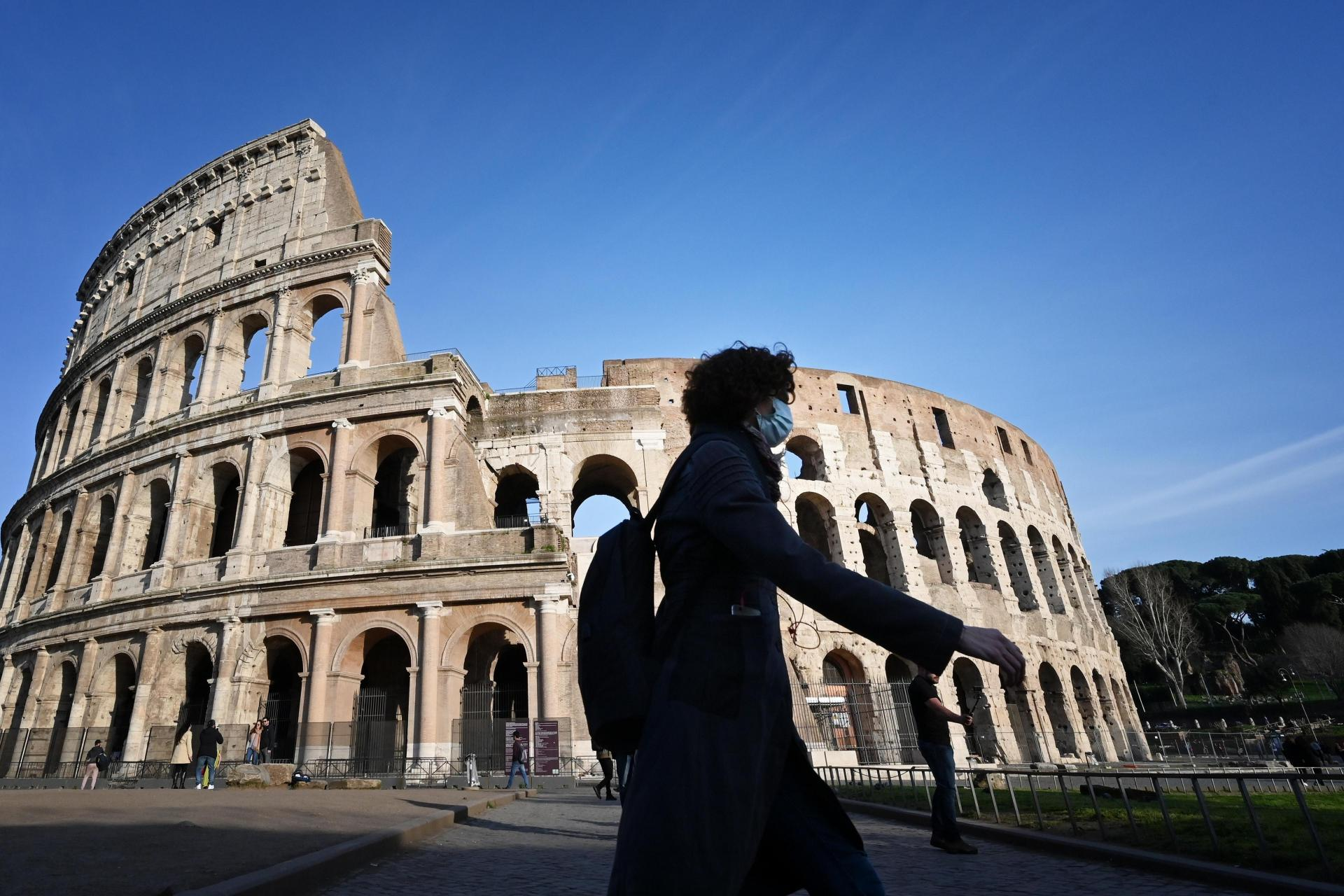 A masked woman walks past a deserted Colosseum in Rome. Photo: AFP