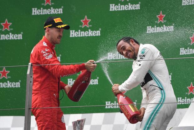 Third-placed Ferrari's German driver Sebastian Vettel (left) sprays champagne at winner Mercedes' British driver Lewis Hamilton (right).