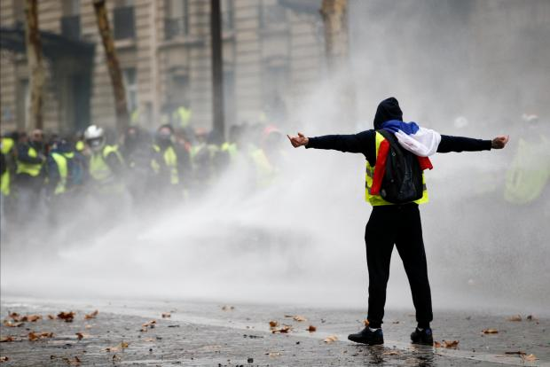 Protesters wearing yellow vests, a symbol of a French drivers' protest against higher diesel taxes, face off with riot police during clashes.