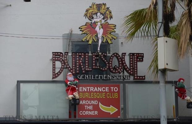 A Father Christmas decoration is hung under a Paceville club sign on December 9. Photo: Matthew Mirabelli