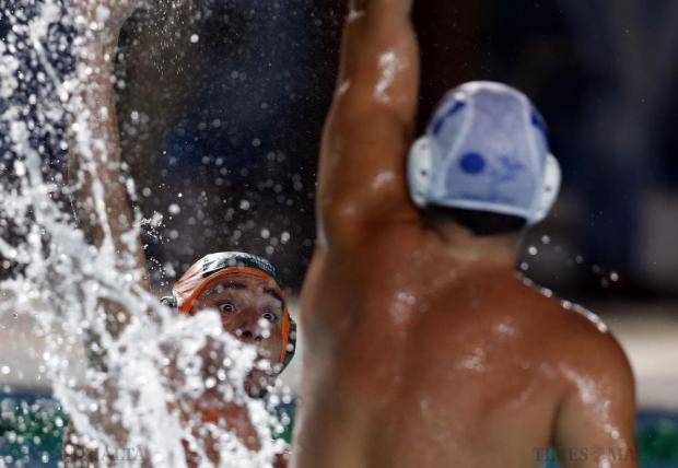 Marsascala's Stephen Micallef (left) tries to pass the ball over Marsaxlokk's Marc Lanzon during their First Division waterpolo match at the National Pool in Tal'Qroqq on August 19. Photo: Darrin Zammit Lupi
