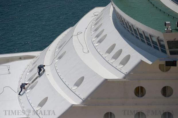 Two workers make their way down a ladder after carrying out work on a cruise liner in the Grand Harbour on August 14. Photo: Matthew Mirabelli