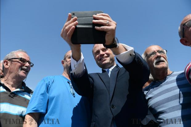 A group of men pose with Joseph Muscat at the Grand Harbour Marina, Birgu on May 23. Photo: Matthew Mirabelli