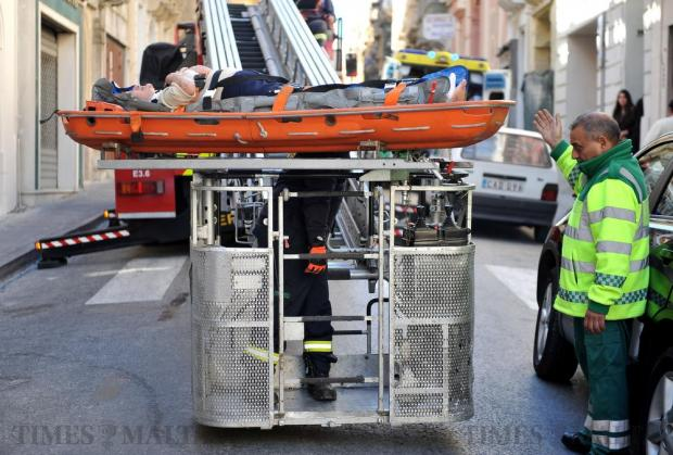 Rescuers use a tower ladder to lower an elderly woman who fell from a roof onto another roof, as a stretcher could not be carried down the stairs of her home in Sliema on February 21. Photo: Chris Sant Fournier