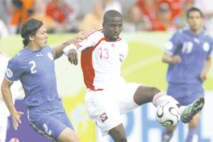 Paraguay`s Jorge Nunez (left) closes in on Trinidad and Tobago`s Cornell Glen during last night`s Group B match.