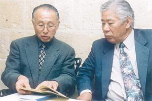 Mr Sasaki (left) discussing a photo album with Mr Michio Endo.