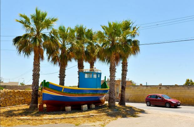 A luzzu fishing boat is nicely parked in a shady spot between six palm trees on May 7. Or have the palm trees been planted purposely later to provide shade for the boat? Photo: Chris Sant Fournier