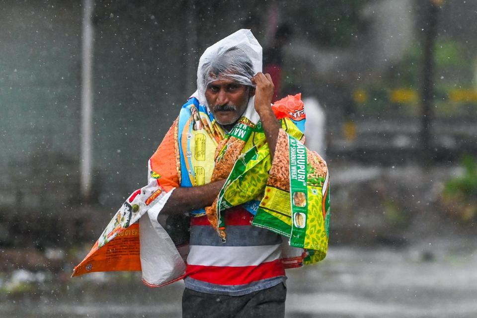 Un hombre se cubre con plásticos mientras camina por una calle en Amreli el 18 de mayo de 2021, después de que el ciclón Tautae azotara la costa oeste de India con fuertes vientos y lluvias torrenciales, dejando al menos 20 muertos.  Foto: Punit Paranjpe / AFP