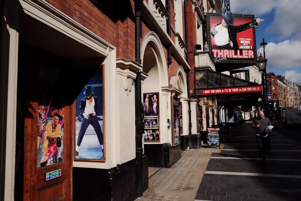 A man walks past West End theatres on an almost deserted Shaftesbury Avenue in London.