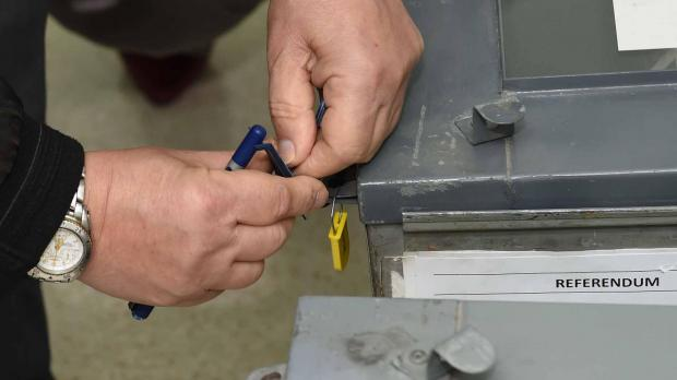 An Electoral Commission official sealing a ballot box this morning. Photo: Jeremy Wonnacott, DOI