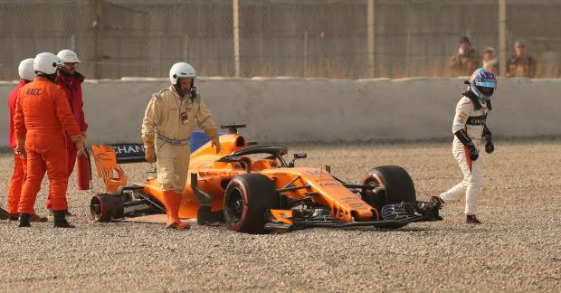 Fernando Alonso of McLaren walks away from his car after a tyre fell off during testing.