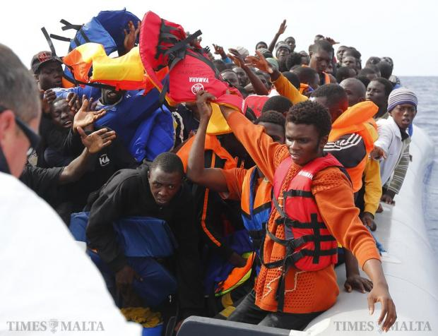 A group of 106 sub-Saharan Africans on board a rubber dinghy reach out for lifejackets tossed to them by rescuers of the NGO Migrant Offshore Aid Station (Moas) off the Libyan coast on October 4. Photo: Darrin Zammit Lupi/Moas