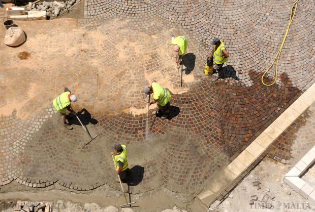 Workers lay new tiling at Castille Square in Valletta on June 10. The square will be fully pedestrianized as part of renovation works ahead of November's Commonwealth summit. Photo: Chris Sant Fournier