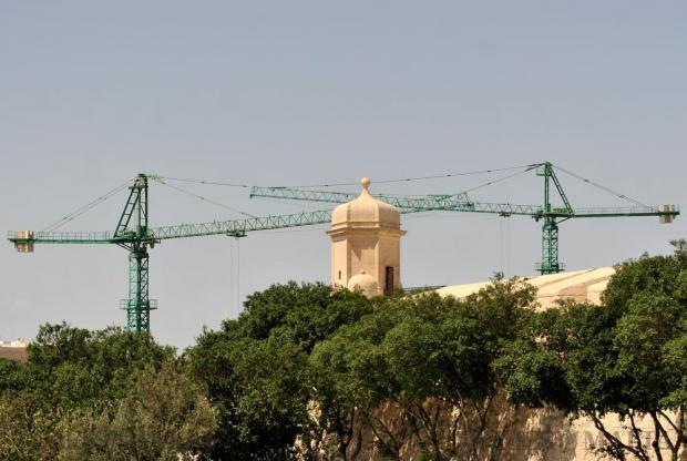 Two tower cranes are seen behind the 'gardjola' watch tower on the St James Counterguard bastions in Valletta on August 31. Photo: Chris Sant Fournier