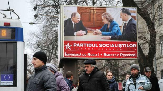 People walking past an election poster for the Party of Socialists, with a picture of party members meeting with Russian President Vladimir Putin, in Chisinau, Moldova, yesterday. Photos: Reuters