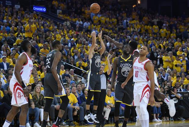 Stephen Curry (centre) of the Golden State Warriors shoots and makes a three-point shot.