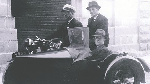 Chairman Harry Simonds de Brett (in sidecar) with founder and managing director Lewis V. Farrugia (pinion rider) being 'chauffeur-driven' in wartime.