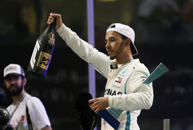 8 Mercedes' Lewis Hamilton celebrates with a trophy after winning the race.