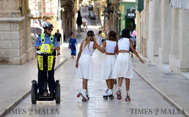 A Police woman on a Segway passes by roller skaters in Valletta on July 02. Photo: Mark Zammit Cordina
