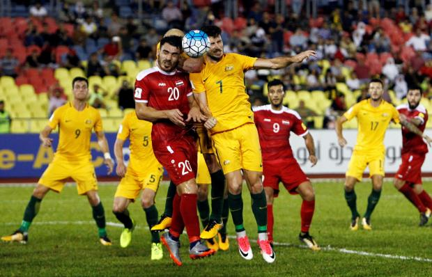 Australia's Mathew Leckie and Syria's Khaled Al Mbayed fight for the ball.