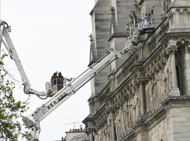 Firefighters secure Notre-Dame Cathedral in Paris on April 16, 2019, in the aftermath of a fire that caused its spire to crash to the ground.