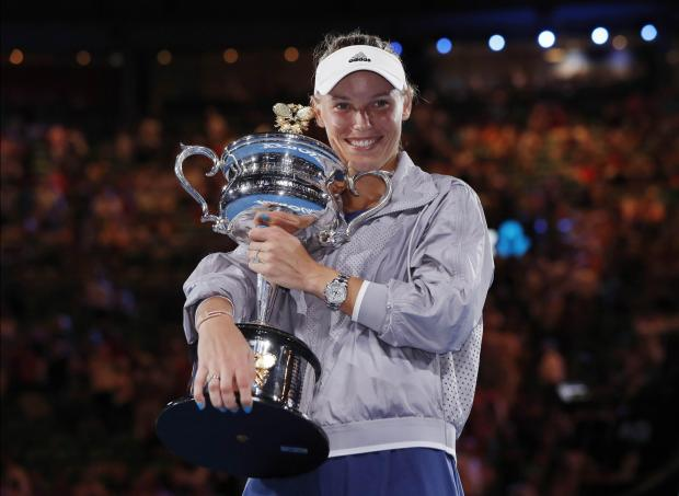 Denmark's Caroline Wozniacki celebrates with the trophy after winning the final against Romania's Simona Halep.
