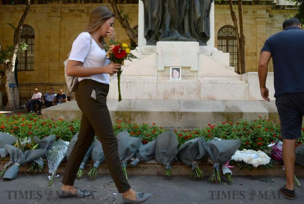 A girl lays flowers at the Great Siege Monument in Valletta on October 18, in a silent commemoration to mark their sorrow at the murder of journalist Daphne Caruana Galizia. Photo: Matthew Mirabelli