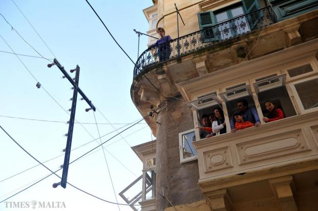 People watch the Good Friday procession from their windows in Valletta on April 3. Photo: Chris Sant Fournier