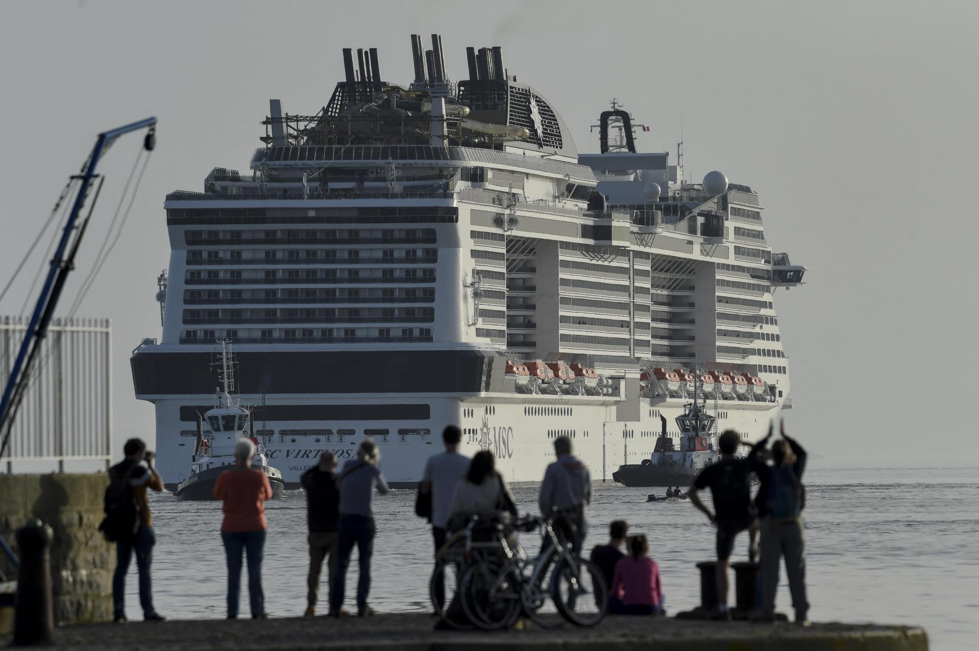 """People watch the departure of Italian operator MSC Cruises new cruise ship MSC Virtuosa for the port of Le Havre and her inaugural journey, at the """"Chantiers de l'Atlantique"""" shipyard in Saint-Nazaire on March 30, 2021. Photo: AFP"""