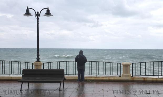 A man watches the rough waves in Sliema on December 18. Photo: Mark Zammit Cordina