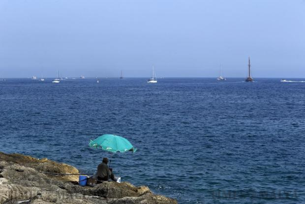 A man patiently fishes in the shade of an umbrella beneath Fort St Elmo as a number of sailing boats take advantage of the weekend's fine weather and sail into the distance on July 10. Photo: Darrin Zammit Lupi