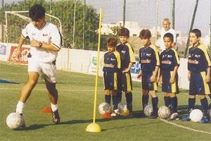 Buzu Soccer School head coach Carmel Busuttil showing ball control skills to his young footballers at St Martin`s. New addition to the school, John Buttigieg, is seen in the background.