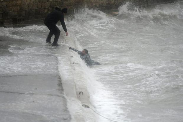 A man is helped out of the sea after waves swept him away at Xemxija. Photo: Jonathan Borg