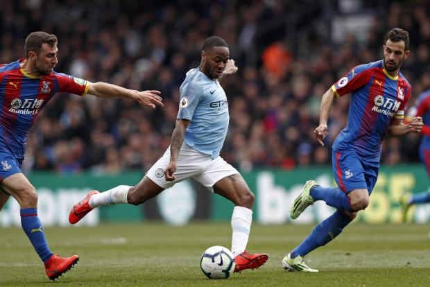 Man. City's Raheem Sterling (centre) rushes through between Crystal Palace's James McArthur (L) and Luka Milivojevic to take a shot.